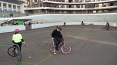 ciclismo : March 17, 2019. Ukraine, Kiev. Bike polo game. group of people team on city bikes are training playing team game in stadium. man on bicycle with stick in his hands kicks ball into the goal.