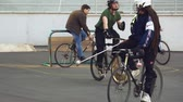 polígono : March 17, 2019. Ukraine, Kiev. Bike polo game. group of people team on city bikes are training playing team game in stadium. man on bicycle with stick in his hands kicks ball into the goal.