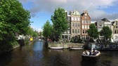 lavanda : July 05 2016: Amsterdam, Netherlands: view of a street and the famous canal Amsterdam city Holland with touristic boat. Netherlands Europe Amsterdam canal street Netherlands Netherlands footage 4K