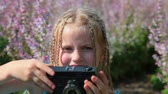 rangefinder : Little girl with a camera on blossoming meadow in spring Stock Footage