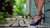 Female legs in high heels in front of an old wooden house closeup