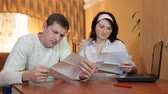 Frustrated young husband and wife who read some bad news in a letter or financial bill at home
