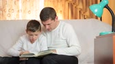 Father and son reading book together sitting on a sofa in the living room Wideo