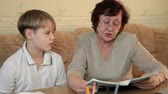 Grandmother with her grandson doing homework sitting at a desk in the living room