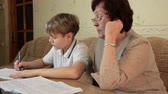 Grandma helping her grandson doing homework sitting at a desk in the living room Wideo