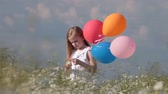 little blonde girl with colorful balloons in lush summer field Wideo