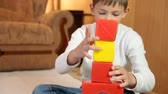 Child playing with colored blocks on floor in the room building a stack