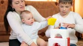 Mother and children playing with colored blocks building the house on floor in the room