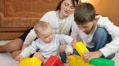 young mother with children playing colored blocks on the floor of living room at home