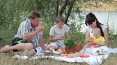 Young family with children spending weekend on the nature eating shashlik at picnic near camp tent