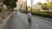 asphalt : Rishon LeZion, Israel - October 4,2014: Unidentified son and father bike in deserted city. Once a year, on Yom Kippur (Jewish Day of Atonement) the country goes quiet as almost all cars stop running