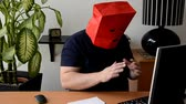 shrink : Man removing red paper bag from his head but there is black balaclava under  it Stock Footage