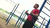 абс : Fit Man Training Abdominal Muscles in Outdoors Gym
