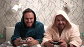 bien jouÉ : Two guys play computer games on the bed in bathrobes and win. Slow motion footage 2 bearded men play video game