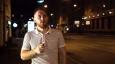 ombretti : Bearded man in striped t shirt smoke electronic cigarette iqos at night on street with cars on background and walking down the street