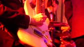 соло : Close up shot of men playing electric guitar on stage at night.
