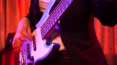 соло : Close up shot of men playing white 5 strings bass guitar on stage at night.