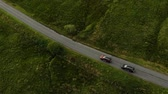 birdseye : Two SUVs drive one after another along country road in field. Aerial view. Stock Footage