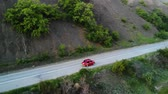 沿岸の : Small red retro car ride on the road near ocean or sea cinematic footage