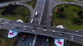 hour : Aerial view of a motorway. Camera move back with a view on car interchange. A lot of cars ride on the 10 lanes motorway.