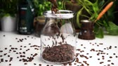 seçim : Slow motion empty transparent jar filled with coffee beans on white table with coffee beans lay on table. Stok Video