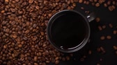Close up slow motion of hot black coffee in black cup on black table with a lot of coffee beans on the table. Smoke is going from cup