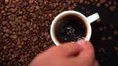 Top view of person hand stirring coffee in white cup with spoon on black table with coffee beans on table. Stockvideo