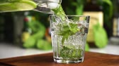 Slow motion mineral water or soda fill glass with lime, mint and ice cubes. Food background. Stockvideo