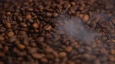 Slow motion close up coffee beans are roasted on a frying pan, smoke comes from coffee beans. Nice background with green plants and coffee pack.