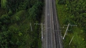 Fly over railroad between forest.
