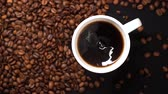 Top view of stirring black coffee in white cup with spoon on black table with coffee beans on table. Stockvideo