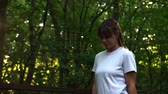 dürtmek : Nice slim girl in white shirt walking in woods or park forward.