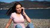Happy attractive girl in pink t-shirt and blue jeans or woman sit on beach and using smartphone talking. Slow motion