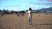 vyděsit : Slow motion of running slim young girl to seaguls and try frighten off them. Nice cloudy blue sky
