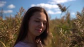 Attractive portrait of young girl in pink t-shirt in field looking in camera in slow motion. Стоковые видеозаписи
