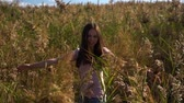 young woman or girl in pink t-shirt and blue jeans spinning in slow motion in field of reed or cane