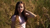 Attractive portrait of young girl in pink t-shirt in field looking in camera. Out of focus and then in focus. Slow motion footage. Стоковые видеозаписи