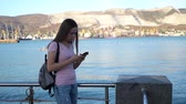 achteraanzicht : Girl in pink shirt and backpack on shoulder using smartphone texting or write text message. Stockvideo