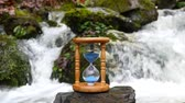 antiguidade : Hourglass on the background of a mountain stream