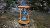 old time : Hourglass on the background of a mountain river