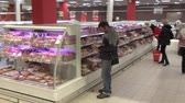 potraviny : Moscow, Russia - 20 May 2016: Man chooses sausages in meat department of supermarket. People buy foodstuffs. Retail Food Industry.
