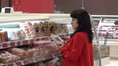 potraviny : Moscow, Russia - 20 May 2016: Woman chooses sausages in meat department of supermarket. People buy foodstuffs. Retail Food Industry. Dostupné videozáznamy