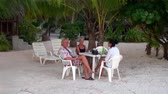 showplace : Tahiti Island French Polynesia - 26 May 2018: Man and two women are drinking wine at a white table on the coast of ocean. Picturesque wild nature nd beautiful landscape. Exotic travel.