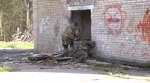 askerler : Moscow, Russia - May 09, 2013: Soldiers in military uniform with weapon run on background of ruined house. Airsoft game for courageous men in Russia.