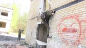 granada : Moscow, Russia - May 09, 2013: Airsoft men in military uniform with a weapon climbs up the ruined house. Sports team game using a copy of a firearm. Stock Footage