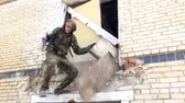 airsoft : Moscow, Russia - May 09, 2013: Airsoft men in military uniform with a weapon climbs up the ruined house. Sports team game using a copy of a firearm. Stock Footage
