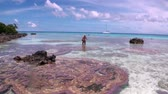 showplace : Tahiti Island, French Polynesia - 26 May 2018: Woman stands in clear water on background of corals and a sailboat. Pink round coral near the coast of island with a tropical climate. Stock Footage