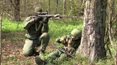 airsoft : Moscow, Russia - May 09, 2013: Players of airsoft is in position in the forest. Sports team game using a copy of a firearm. People in military uniforms with weapons at the exercises. Stock Footage