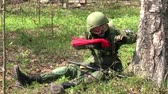 combativo : Moscow, Russia - May 09, 2013: Airsoft player is in position in the forest. Sports team game using a copy of a firearm. People in military uniforms with weapons at the exercises.