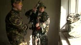 airsoft : Moscow, Russia - May 09, 2013: Airsoft player is in position is in position in a destroyed house. Sports team game using a copy of a firearm. People in military uniforms with weapons at the exercises. Stock Footage